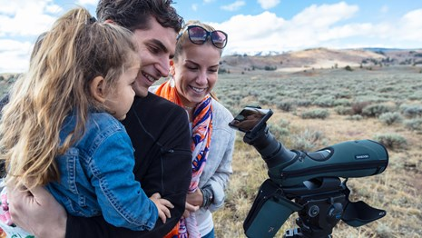 A man, woman and child look into a phone mounted to a spotting scope in a sagebrush covered valley