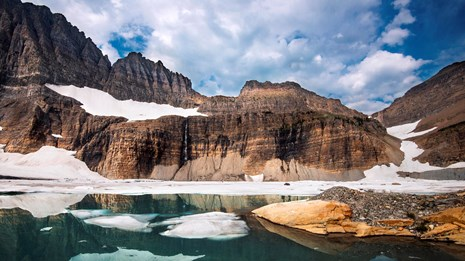 Photo of snow partially melted on a lake surrounded by dramatic rock formations.