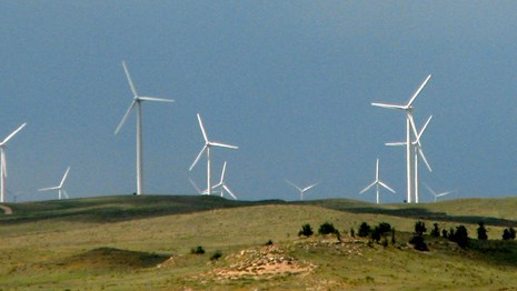 Image of green field with large white wind turbines.