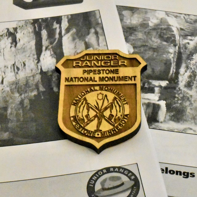 A Jr. Ranger badges on top of Jr. Ranger booklets