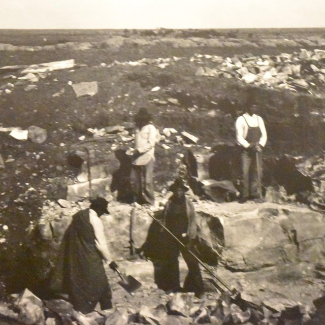 Four men standing in a quarry