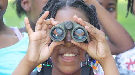 A small child looking through binoculars