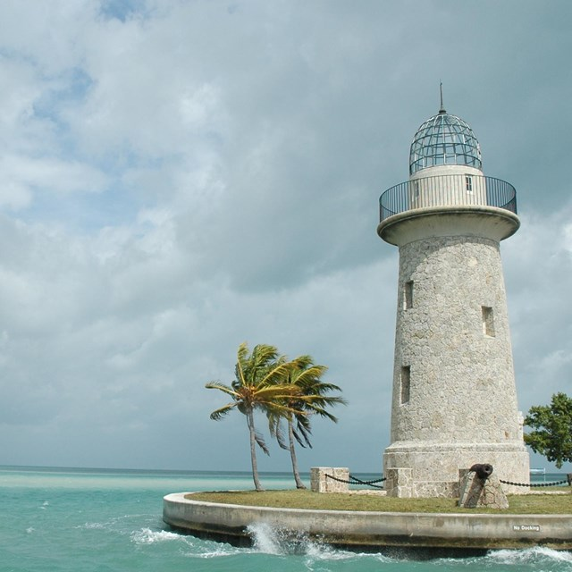 green tropical water on left with lighthouse and palm trees on rights