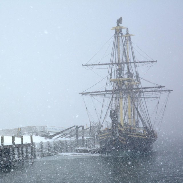 a wharf with tall ship on right; snowing