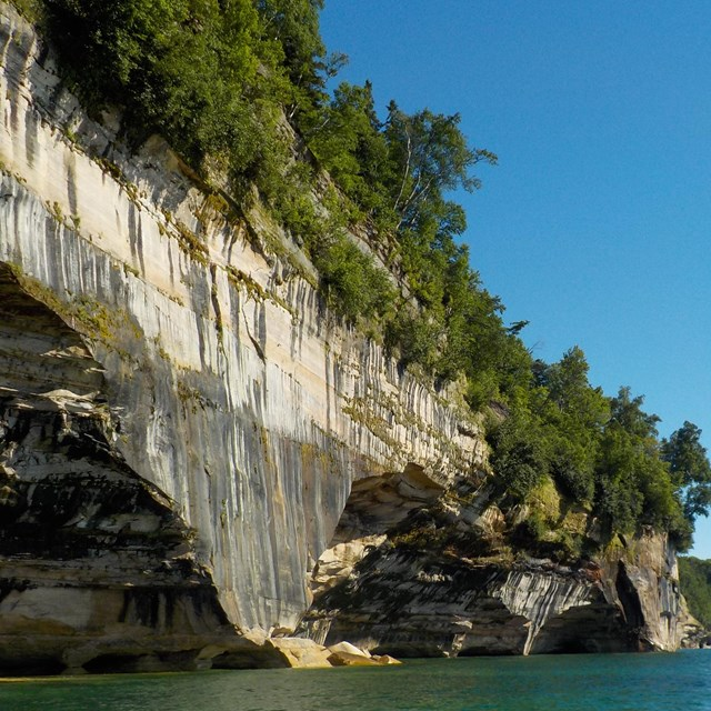 Tree-topped black streaked cliff wall with eroded out portions at the Lake Superior waterline.