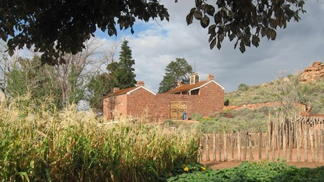 A sandstone fort, red cliffs and garden plants in front of a baby-blue sky.