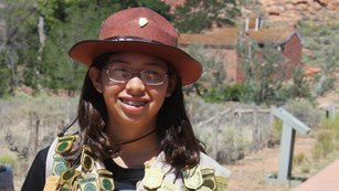 A young girl stands in front of a fort wearing dozens of Junior Ranger badges.