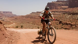 Park ranger on a mountain bike in a desert landscape
