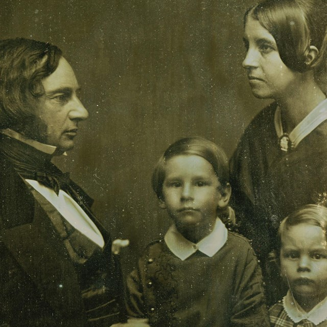 Group portrait of a man and woman in profile and two small boys facing camera.