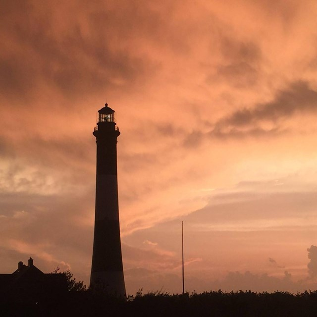 Silhouette of lighthouse against peach colored clouded sky.