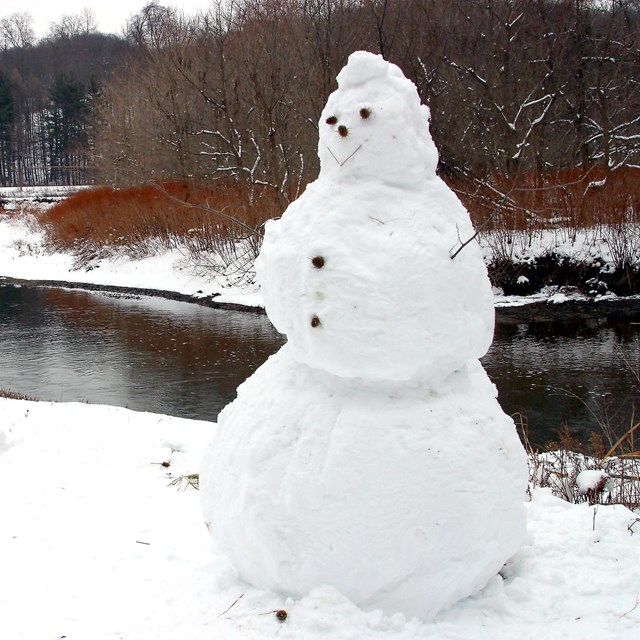 Snowman along a snow-covered towpath