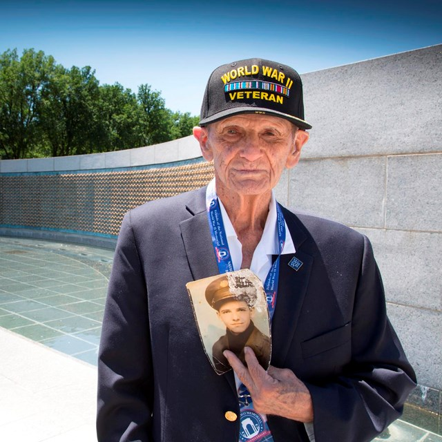 World War II Veteran holding an older photo of himself while standing at the WWII Memorial