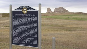 A large sign stands in front of a distant rocky bluff.