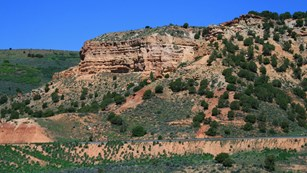 A towering red sandstone bluff, lightly vegetated, under a blue sky.