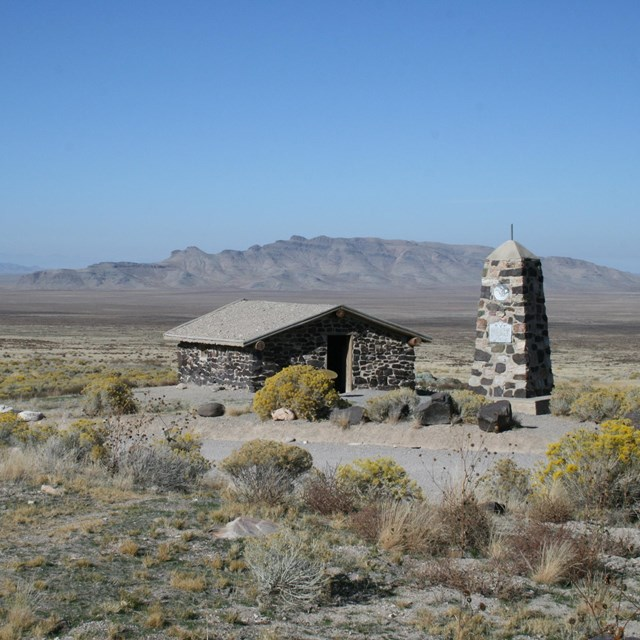 A stone building sits in an expansive desert setting.