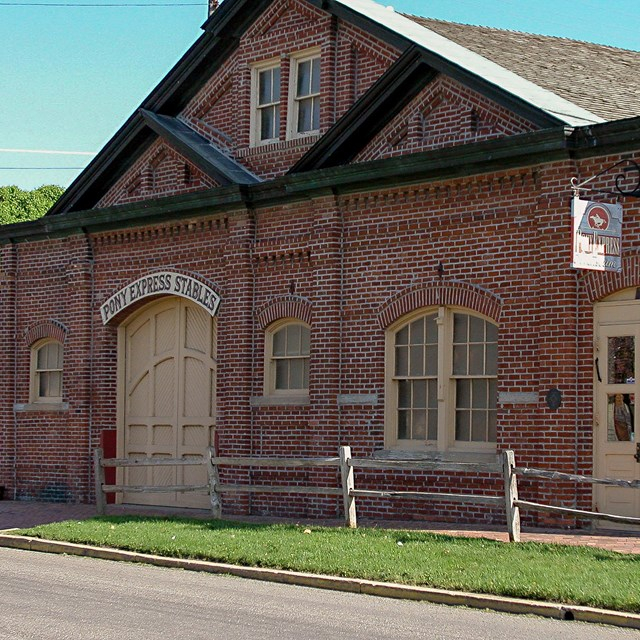 A large, one-story red brick stables with cream colored doors.