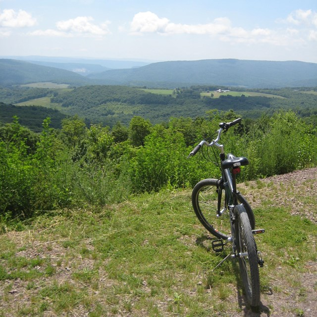 A bicycle standing overlooking a valley of rolling green hills and trees with smoky blue mountains.
