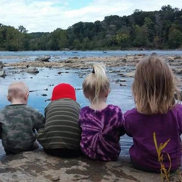 Four children sit on a rock along the water