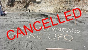 The word cancelled superimposed over a photo of a sand sculpture of an unidentified flying object.