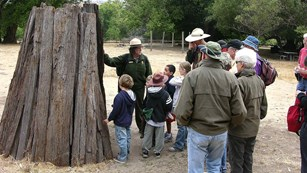 A park ranger with 15 students and parents at a wooden structure in a replica Coast Miwok village.