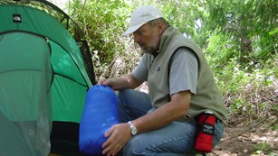 A camper setting up his tent.