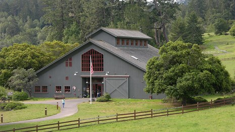 The Bear Valley Visitor Center. A gray, barn-like structure surrounded by oak and Douglas fir trees.