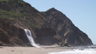 Alamere Falls descending onto Wildcat Beach with the craggy Double Point in the background.