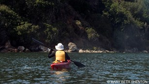 A woman wearing a yellow life-jacket and a white hat paddling a red kayak.