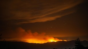 Smoke rises above a ridge and reflects orange light from a wildfire burning on the ridge's far side.