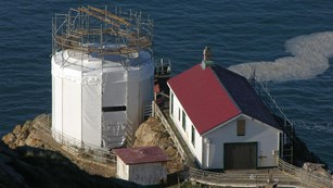 White structures, some with red roofs, surrounded by scaffolding perched on a cliff above the ocean.