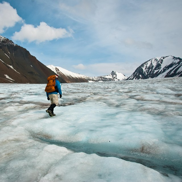 Man traverses ice field surrounded by snowy mountain peaks.