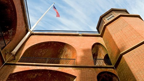 Flag flying over masonry arches of Fort Point