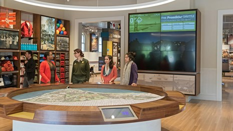 A ranger and visitors look at a 3-D map of the Presidio in the visitor center