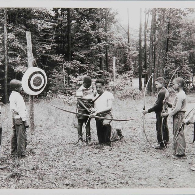 Young campers learning archery in a historic 1930s photo