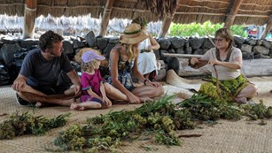 A family sitting on a lauhala mat learns how to make a lei