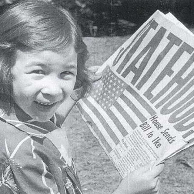 Historic photo of excited girl holding newspaper that says