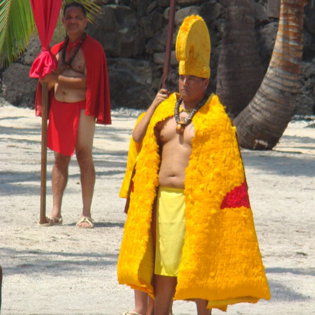 Man in feathered cloak and helmet of the aliʻi (royalty) walks in the Royal Grounds