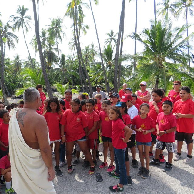 A man in traditional clothing greets a group of school children wearing red t-shirts.