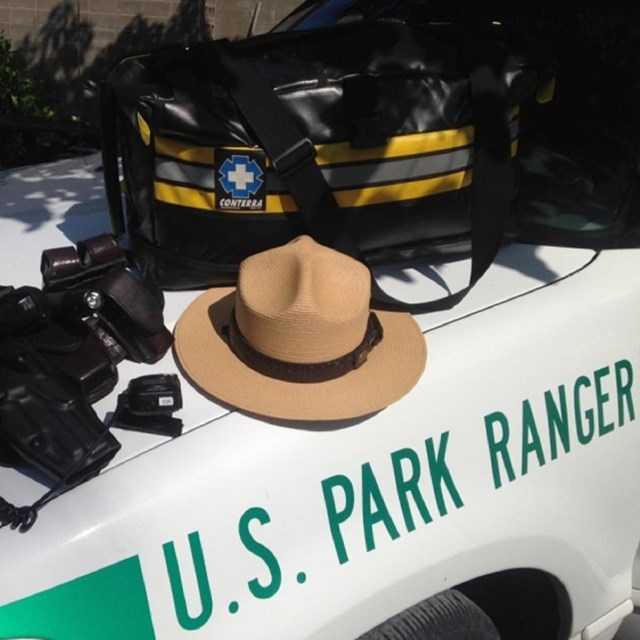 A ranger hat and equipment laid out on the hood of a U.S. Park Ranger vehicle.
