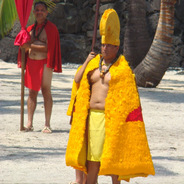 Man in feathered cloak and helmet of the aliʻi (royalty) walks through the Royal Grounds