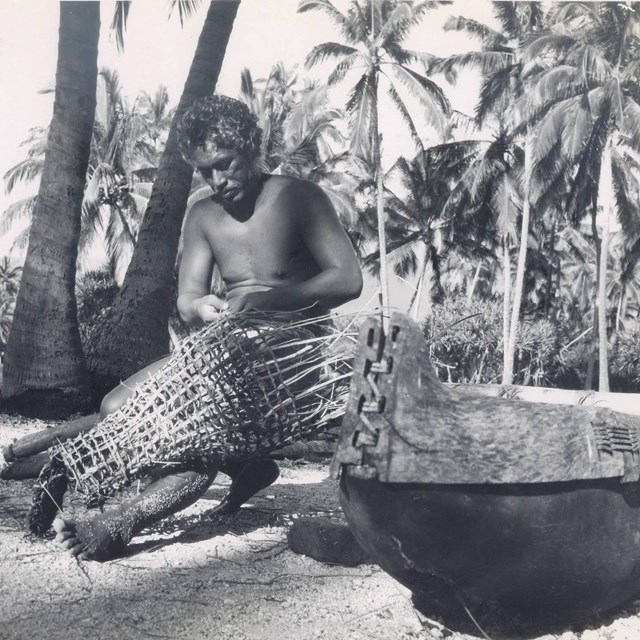 Man in traditional clothing weaves a fishtrap while sitting under coconut trees in the Royal Grounds