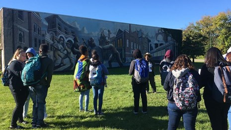 Group of students listen to a ranger in front of a Pullman mural.