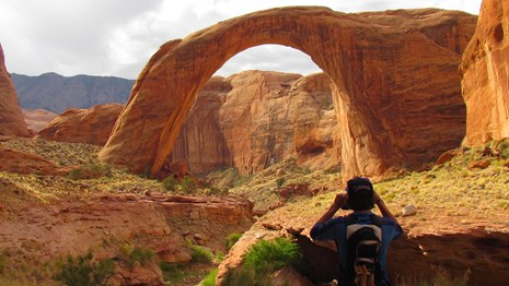 A person has his back to Rainbow Bridge as he takes a picture.