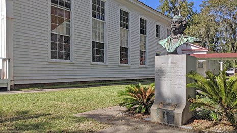 Sculpture of Robert Smalls next to a white church