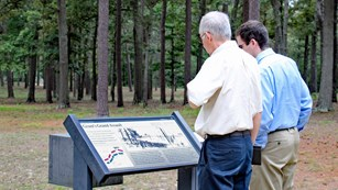 Two visitors examine an outdoor wayside sign.
