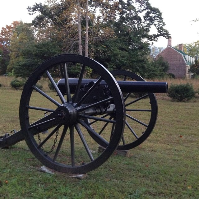 Civil War cannon in foreground, brick colonial house in background
