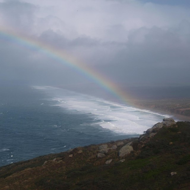 A view from the Lighthouse Visitor Center of Point Reyes Beach and a rainbow during a winter storm.