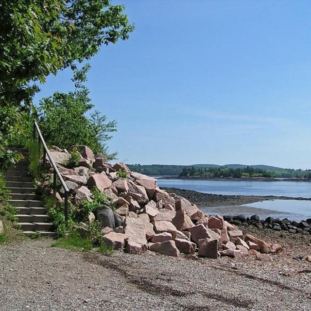 rocky beach with a view across the river toward Saint Croix Island.