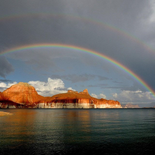 Credit: NPS Photo/ Ross Kantra On Lake Powell, a rainbow arches over the buttes in Padre Bay.