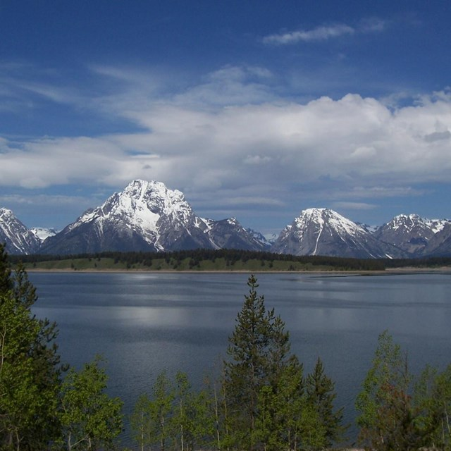 Mount Moran with snow and Jackson Lake with clouds.